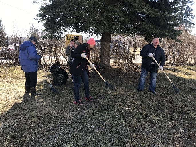 Участники субботника сгребают листву и убирают, скопившийся за зиму, мусор